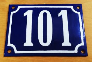 Ein rechteckiges Emaille-Blechschild, leicht konvex gewölbt, kobaltblauer Hintergrund, die Zahl 101 und ein Rahmen ist in Weiß gehalten. Ein Schraubenloch in jeder Ecke.
